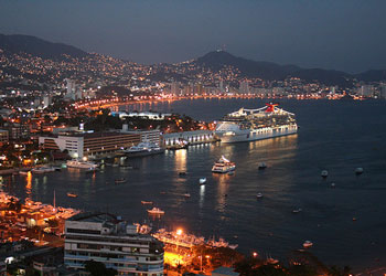 Carnival Spirit lit up at dusk in Acapulco Bay
